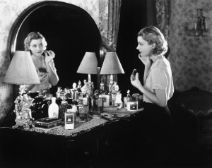 Young woman in front of her vanity applying make-up